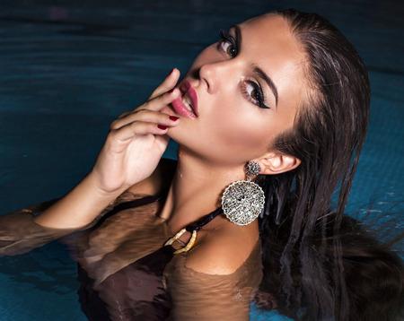 mojar: Foto de la manera de la mujer hermosa chica con el pelo oscuro en bikini relajante en la piscina por la noche Foto de archivo