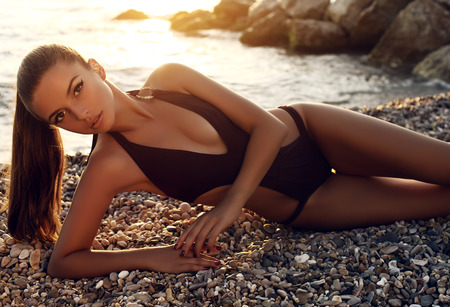 fashion photo of beautiful sexy girl with dark hair in black swimsuit posing on sunset beach