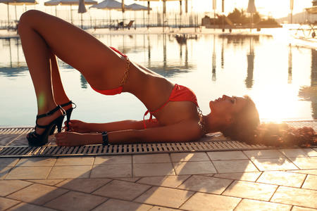 fashion photo of sexy beautiful girl with perfect body doing yoga pose beside a swimming pool
