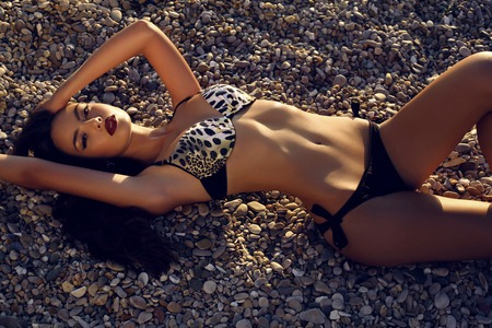 tanned body: fashion photo of sexy girl with tanned body in bikini posing on sunset beach Stock Photo