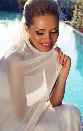 fashion photo of beautiful smiling bride with blond hair in elegant wedding dress posing beside a swimming pool photo