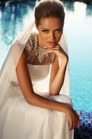 sexy bride: fashion photo of beautiful bride with blond hair in elegant wedding dress posing beside a swimming pool Stock Photo