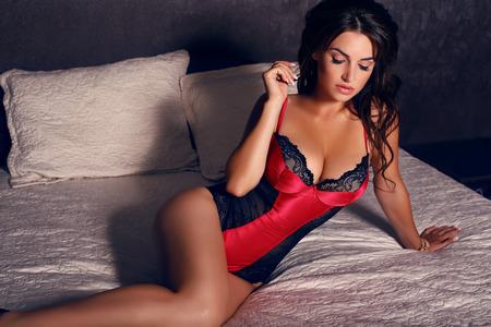 Мода фото секси женщина с черными волосами в нижнем белье позирует в спальне