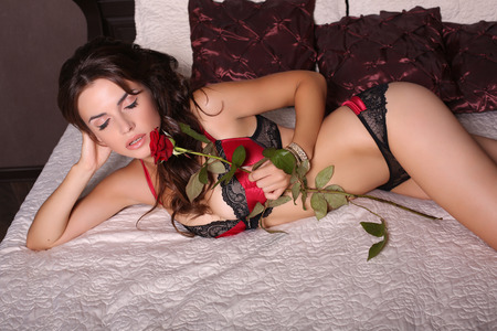 fashion photo of sexy beautiful girl with dark hair in lace lingerie lying on bed in bedroom,holding a one red rose photo