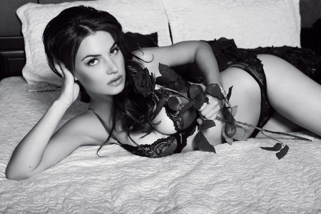 black and white fashion photo of sexy woman with dark hair in lingerie lying on bed in bedroom photo