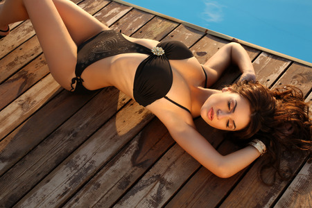 fashion photo of sexy beautiful girl with dark hair in elegant swimsuit relaxing beside a swimming pool photo