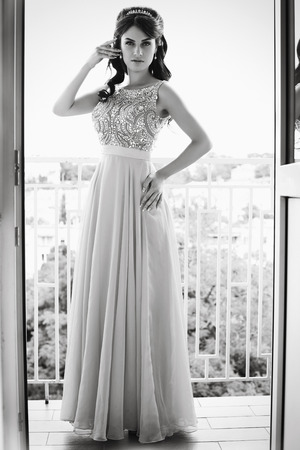 black and white photo of beautiful bride in luxurious dress with diadem posing on balcony photo