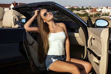 sexy shorts: fashion photo of beautiful sexy girl with long dark hair in jeans shorts and aviator sunglasses posing in luxury cabriolet Stock Photo