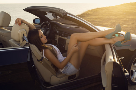 chica sexy: Foto de la moda de la hermosa chica sexy con el pelo oscuro posando en descapotable de lujo en rayos del atardecer Foto de archivo