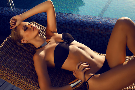 traje de bano: Foto de la moda de la hermosa mujer morena con el pelo rubio en un elegante bikini negro de relax al lado de una piscina Foto de archivo