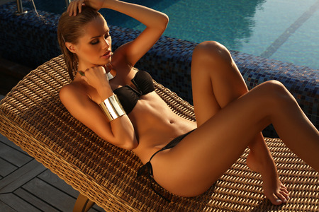 fashion photo of beautiful tanned woman with blond hair in elegant black bikini relaxing beside a swimming pool on wood wicker chair  Stock Photo