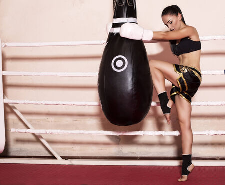 photo of sexy sportive girl with dark hair in sport clothes and boxer gloves posing on ring photo
