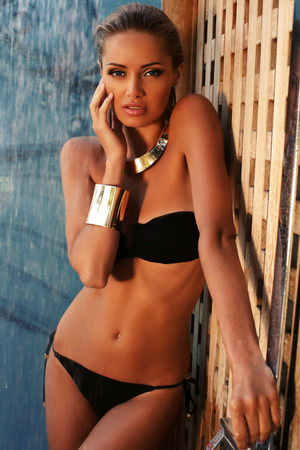 rubia: Foto de la manera de la mujer hermosa chica con el pelo rubio en traje de ba�o negro que toma la ducha en la playa Foto de archivo