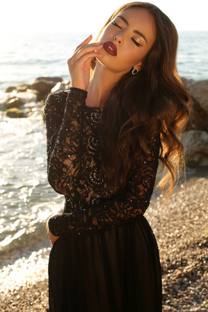 sequins: fashion photo of sensual beautful woman with dark hair in luxurious lace dress posing on summer beach in sunlight rays Stock Photo