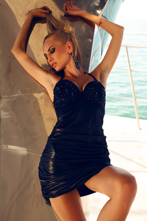 tanned girl: fashion photo of sexy woman with blond hair in luxurious black dress posing beside a metallic wall Stock Photo