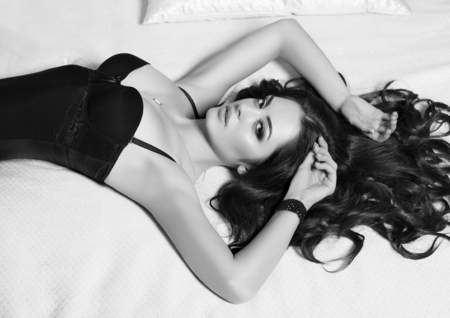 black and white fashion portrait of sexy woman with long black hair in corset lying on bed Stock Photo