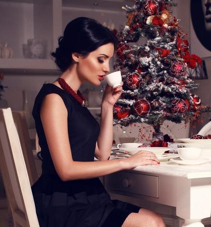 fashion photo of beautiful elegant woman with black hair drinking tea. Decorated Christmas tree on background photo
