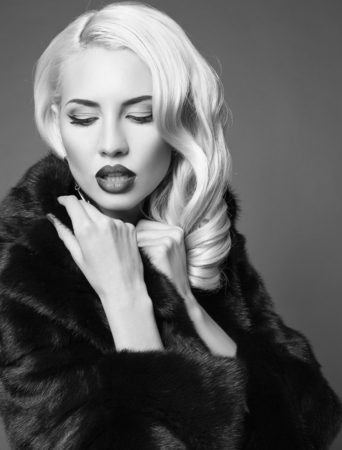 sexy glamour: black and white fashion portrait of sexy glamour woman with blond hair in luxurious black fur coat posing in studio Stock Photo