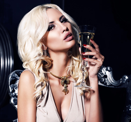 fashion portrait of sexy beautiful woman with blond hair holding a glass of champagne Stock Photo