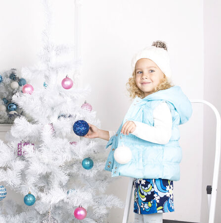 beautiful photo of cute little girl 5 years old with blond curly hair decorating Christmas tree at home photo