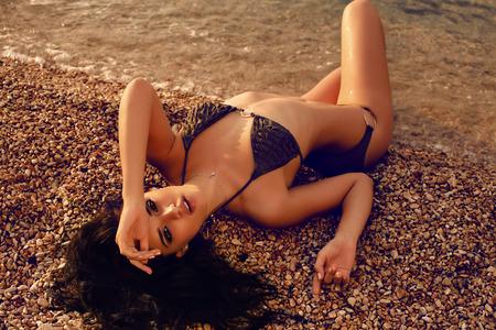 niñas en bikini: moda foto al aire libre de la hermosa mujer sexy con el pelo oscuro en bikini posando en la playa de verano