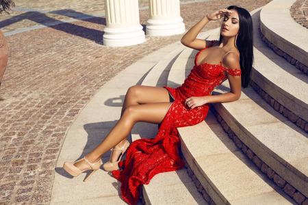 公園の階段でポーズ豪華なエレガントなドレスに黒い髪とセクシーな美しい女性の屋外写真をファッションします。