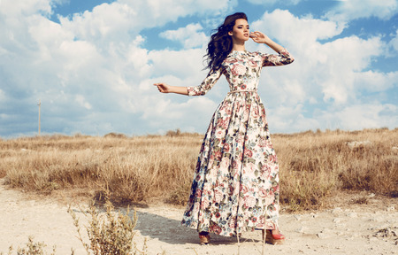 fashion outdoor photo of beautiful woman with dark curly hair in luxurious floral dress posing in summer field Stok Fotoğraf