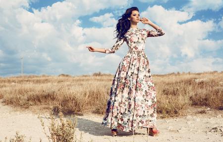 mode utomhus foto av vacker kvinna med mörkt lockigt hår i lyxig blommig klänning poserar i sommar fält