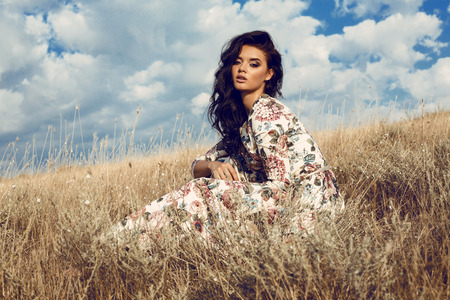 fashion outdoor photo of beautiful woman with dark hair in elegant floral dress posing in summer field