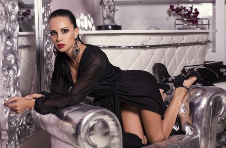 divan: Foto de la moda de la mujer atractiva con el pelo oscuro en vestido negro posando en el interior de lujo