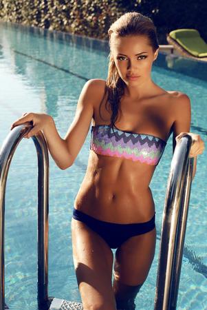 mojado: moda foto al aire libre de la hermosa mujer sexy con el pelo rubio en bikini relajante en la piscina