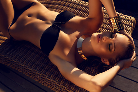 sexy photo: fashion outdoor photo of sexy beautiful woman with blond hair in elegant black bikini with accessories relaxing on summer beach
