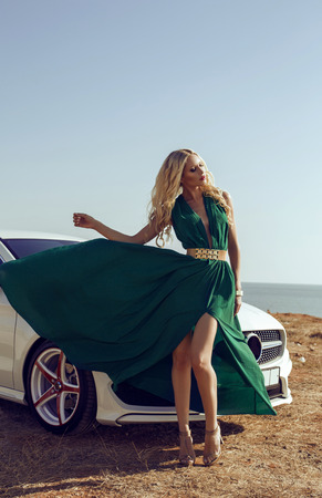 sexy glamour: fashion outdoor photo of sexy glamour woman with long blond hair in elegant green dress posing beside a luxury auto Stock Photo