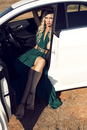 sexy glamour: fashion outdoor photo of sexy glamour woman with long blond hair in elegant green dress posing in white luxury auto