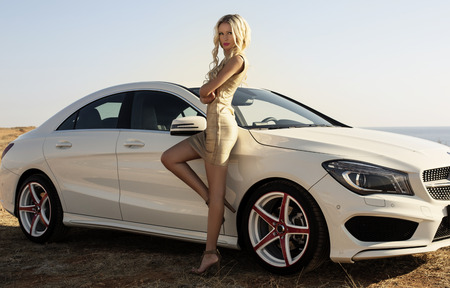 sexy girl: fashion outdoor photo of beautiful glamour woman with long blond hair in elegant gold dress posing beside a luxury car