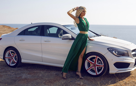 fashion outdoor photo of sexy glamour woman with long blond hair in elegant green dress posing beside a luxury auto Stock Photo
