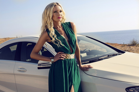 fashion outdoor photo of sexy glamour woman with long blond hair in elegant green dress posing beside a white luxury auto Stock Photo