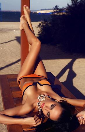fashion outdoor photo of beautiful sensual girl with dark hair in bikini relaxing on summer beach