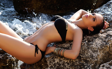 sea sexy: fashion outdoor photo of sexy beautiful woman with dark hair in black bikini relaxing on summer beach Stock Photo
