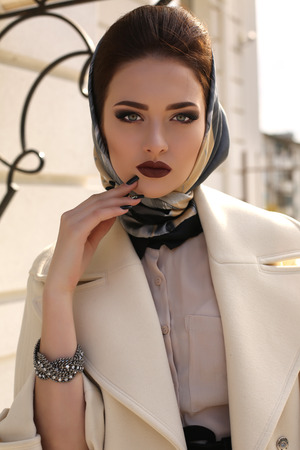 head scarf: fashion outdoor photo of beautiful young woman with dark hair and bright makeup,wearing elegant beige coat and silk scarf on head Stock Photo