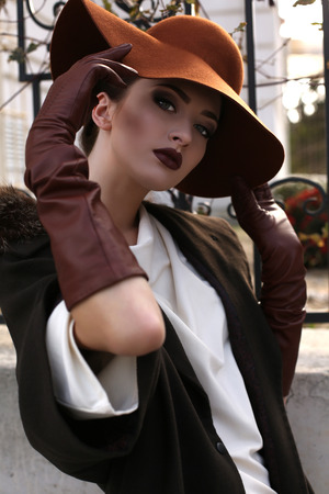 fashion outdoor photo of beautiful young woman with bright makeup wearing elegant coat with fur,felt hat and leather gloves