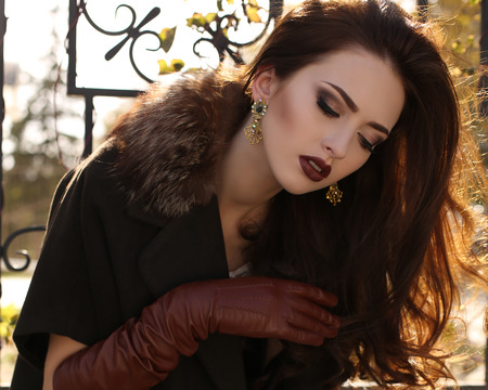 fashion outdoor photo of beautiful elegant girl with dark hair wearing wool coat with fur and leather gloves Stock Photo