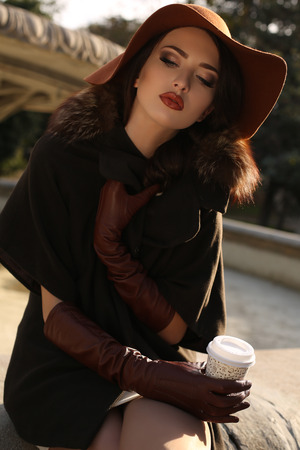 fashion outdoor photo of beautiful ladylike woman wearing elegant coat with fur,felt hat and leather gloves,holding a paper cup of coffee in her hand