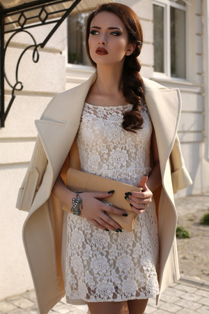 fashion outdoor photo of beautiful young woman with dark hair and bright makeup wearing elegant wool coat and lace dress