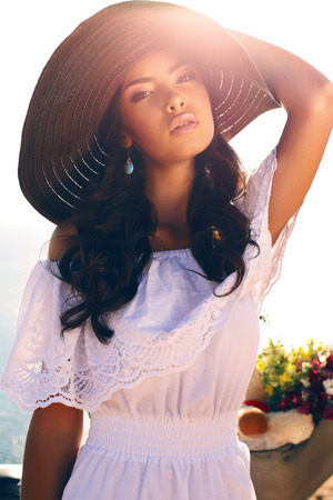 fashion outdoor photo of beautiful sensual girl with dark curly hair in elegant hat and white dress posing on sea coast Stock Photo