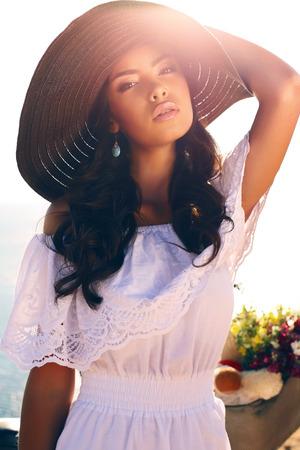 fashion outdoor photo of beautiful sensual girl with dark curly hair in elegant hat and white dress posing on sea coast Zdjęcie Seryjne