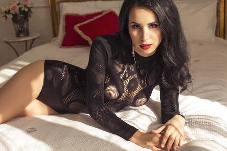 fashion interior photo of sexy beautiful woman with dark hair in lace lingerie lying on bed in bedroom photo