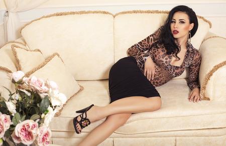 divan: moda foto interior de la mujer hermosa sensual con el pelo oscuro con un vestido elegante y zapatos acostado en el diván en el dormitorio