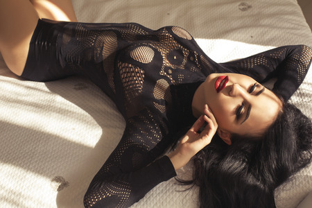 fashion interior photo of beautiful sensual girl with dark hair in black lace lingerie lying on bed in bedroom