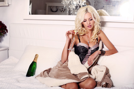fashion interior photo of beautiful sensual woman with blond hair in lingerie corset lying on bed with glass of champagne